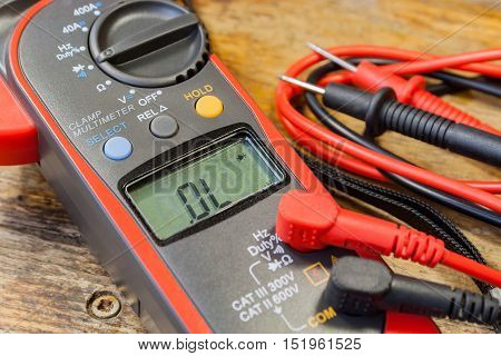 Clamp multimeter with accessories on a table in a workshop