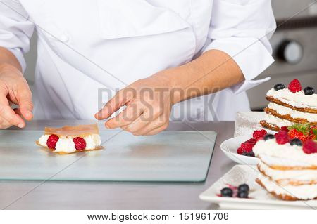 Pastry chef finishing a delicious puff pastry