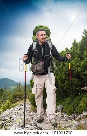 Hiker. Happy hiker. Hiker mountain. Hike.Hiking. Concept success. Hiker sunset. Hiker smiling. Tired tourist. Tired hiker. Concept freedom. Concept inspiration. Winning life goal. Healthy lifestyle. Summer. Nature. Picturesque landscape.
