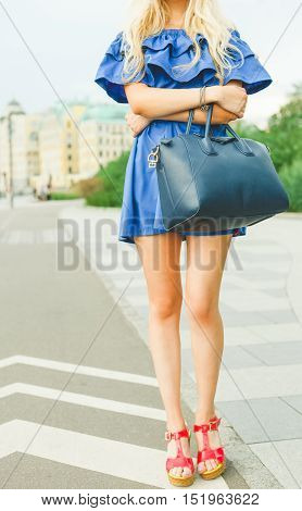 Outdoor summer smiling lifestyle portrait of pretty young woman with big blue handbag and hi heels shoes. Long blond hairs, blue outfit in park. Part of body. Girl, style and fashion. Girl, style and fashion.