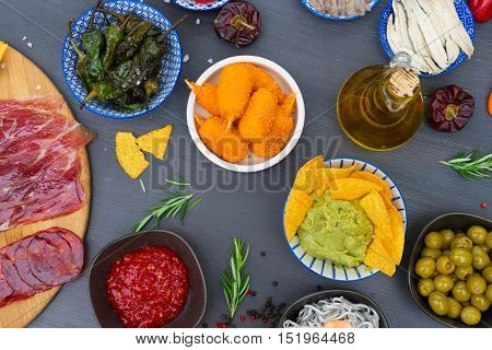 Table with spanish tapas - green peppers padron, jamon, croquetes, guacamole and olives, top view of picnic table