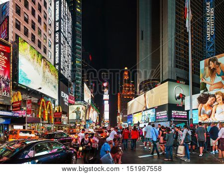 NEW YORK CITY - SEPTEMBER 05: Times square with people in the night on October 5 2015 in New York City. It's major commercial intersection and neighborhood in Midtown Manhattan at the junction of Broadway and 7th Avenue.