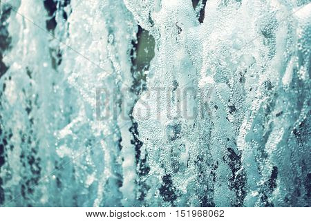 Powerful water jets of city fountain with bubbles and foam.