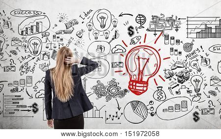 Woman scratching head looking at concrete wall with light bulb and business sketches. Concept of looking for solution