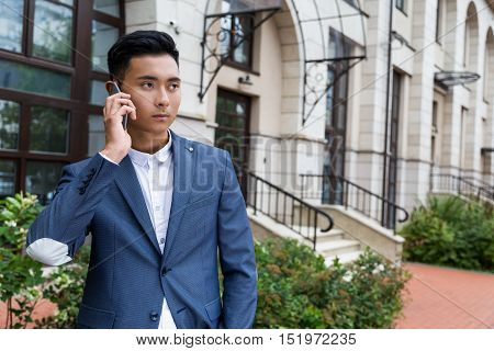 Serious Asian businessman talking on his mobile phone. Concept of never showing your emotions to anybody.