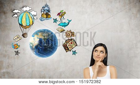 Girl in tank top standing near planet Earth surrounded by travelling sketches. Concept of seeing the world.