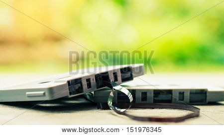 Cassette tape over wooden table with tangled ribbon nature background vintage style