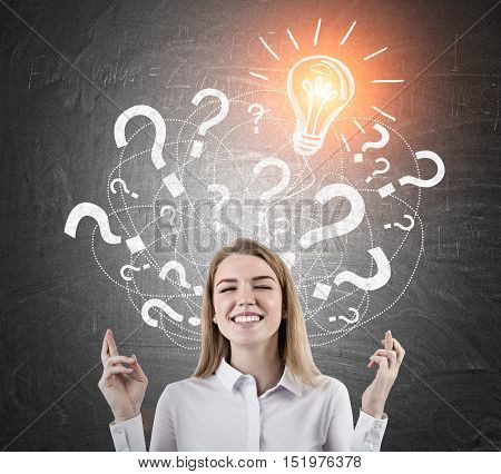 Close up of woman with crossed fingers standing against blackboard with light bulb sketch and question marks. Concept of solution finding.