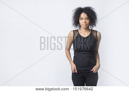 Serious African American girl is standing with her hands in the pockets and looking at the viewer. White background. Mockup