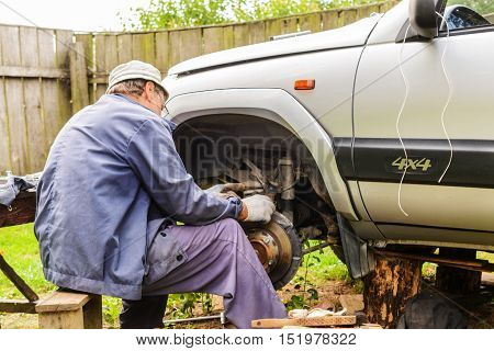 The Mechanic Is Repairing The Front Suspension Of The Car At Home.