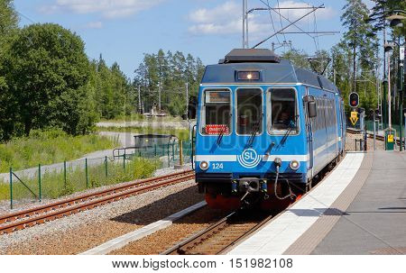 Rydbo, Sweden - July 6, 2016: A blue passenger train in traffic for SL on the narrow gauge railway Rolagsbanan with ine number 28S with final destination Stockholm Ostra station at Rydbo station.
