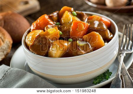 A delicious bowl of rich and hearty beef stew with potato turnip carrot celery and peas.