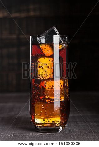 Glass of cola soda with ice cubes on wooden board background
