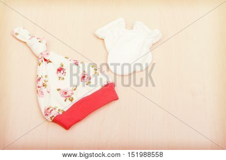 Baby goods. Children's clothing, hat with flowers and white gloves on the background of the changing table. Baby clothes