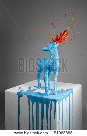 Blue deer sculpture with magic horns on white pedestal