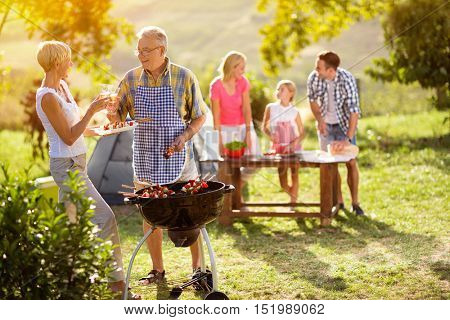 smiling grandparents drink wine by the barbecue for family