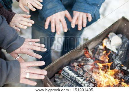 Closeup of Hands of The Group of People Standing Together Near Bonfire and Warming Themself. Horizontal Image Composition