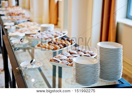 glass table served with white dishes and pastries
