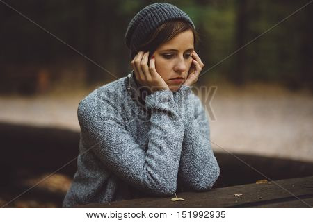 Portrait of sad, depressed woman sitting alone in the forest. Solitude or depression concept. Millenial dealing with problems and emotions.