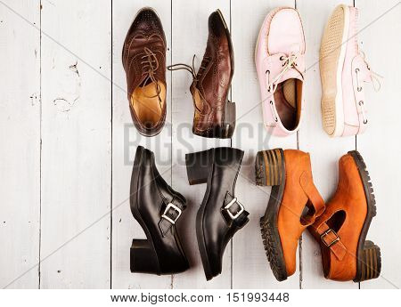 Set Of Different Unisex Shoes On White Wooden Background