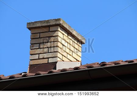 Roof detail of a detached house with red roof tile and beige chimney against the sky with place for your text - copyspace