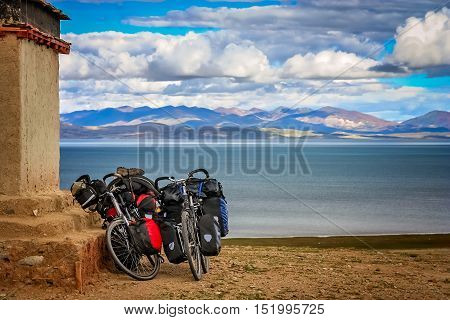 Two cycle touring loaded bicycles rested on the wall of a small old tibetan monastery on a hill above holy Lake Manasarovar, Tibet, China