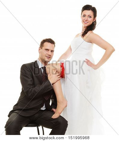 Wedding day. Full length happy newly married couple groom and sexy bride in red garter on leg. Isolated on white background