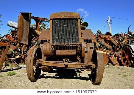 BARNESVILLE, MINNESOTA, Sept 26, 2016: The old John Deere rusty tractor in front of a scrap iron pile is a is a product of John Deere Co, an American corporation that manufactures agricultural, construction, forestry machinery, diesel engines, and drivetr