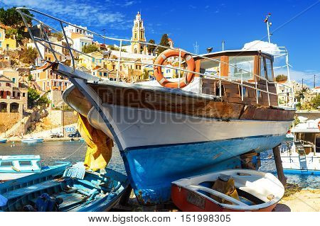 Old fishing Boats at Simi , background of beautiful multi-colored buildings in island
