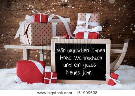 Chalkboard With German Text Frohe Weihnachten Und Ein Gutes Neues Jahr Means Merry Christmas And Happy New Year. Sled With Christmas Decoration And Snowflakes. Presents On Snow With Wooden Background.