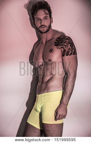 Handsome shirtless muscular man, standing, on light background in studio shot