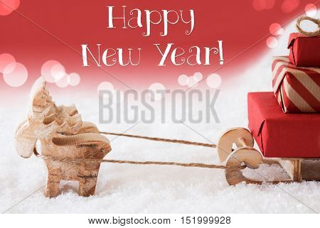 Moose Is Drawing A Sled With Red Gifts Or Presents In Snow. Christmas Card For Seasons Greetings. Red Christmassy Background With Bokeh Effect. English Text Happy New Year