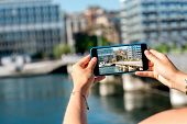 Photographing with phone riverside with buildings in Geneva city in Switzerland poster