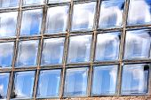 Background image shows sky reflected in rectangle panes of glass. Window is made of individual panes of thick glass. poster
