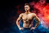 Close up on perfect abs. Strong bodybuilder with six pack. Man with perfect abs, shoulders, biceps, triceps and chest, personal fitness trainer flexing his muscles in blue, red smoke poster