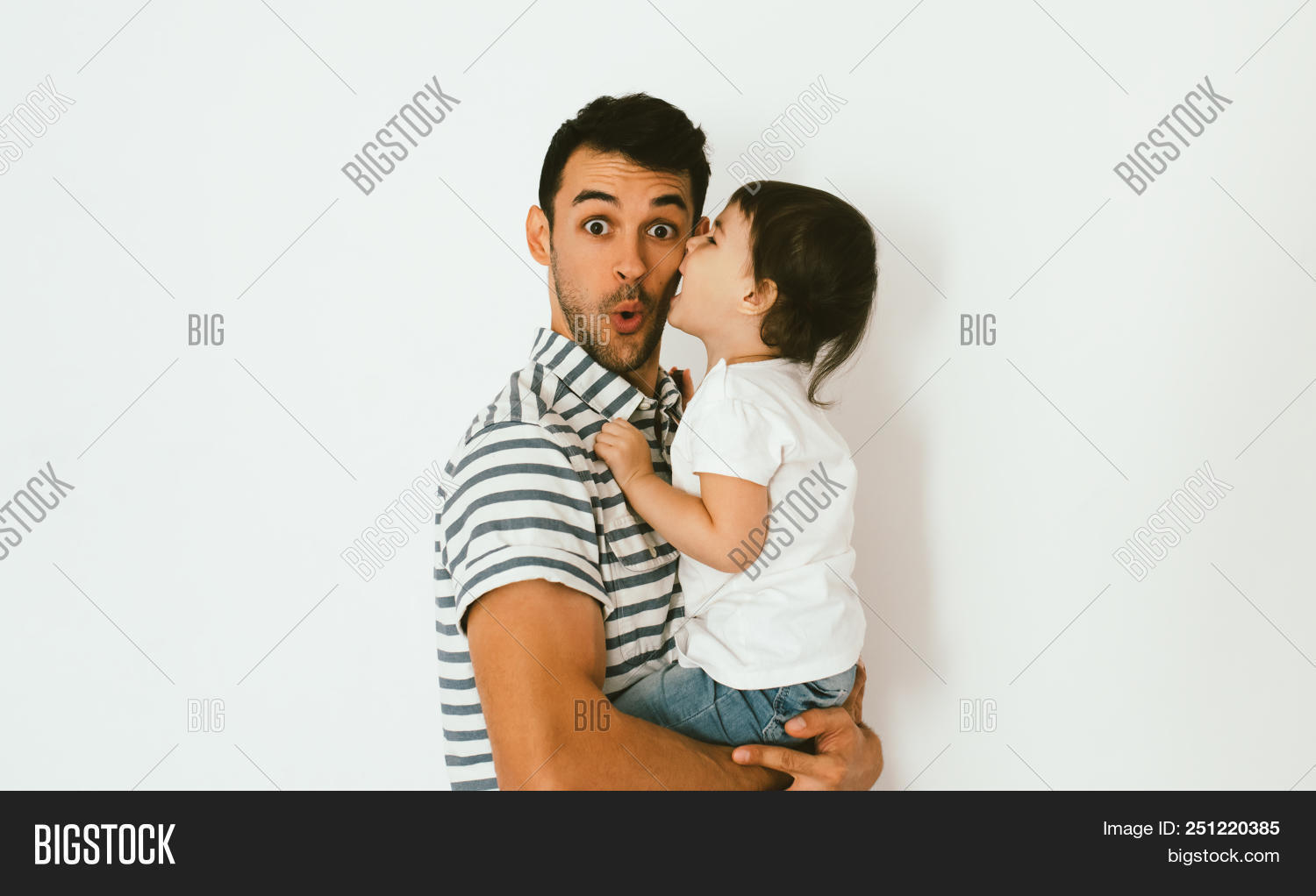 21535efe Cute toddler girl daughter kiss her surprised handsome father on cheek.  Young dad embrace his child. Handsome father with little girl.