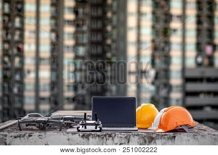 Drone, remote control, laptop computer and protective helmet at construction site. Using unmanned aerial vehicle (UAV) for land and building site survey in civil engineering project. poster