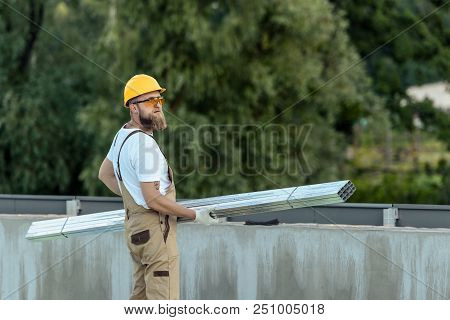 builder in protective googles and hardhat carrying metal structures at construction site poster