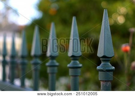 Weapon Lookalike Green Fence With Sharp Edges In A Row Signifying Protection And Also Hostility