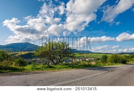 Road Through Beautiful Countryside. Town In The Valley At The Foot Of The Mountain Ridge. Wonderful
