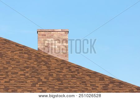 Red brick chimney on shingle roof od new modern house under blue sky on sunny day in summer