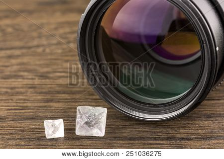 Fluorite Crystals And Camera Lens On A Dark Brown Table