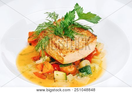 Cooked Red Fish Salmon Steak With Fried Vegetables Garnish On White Plate Background