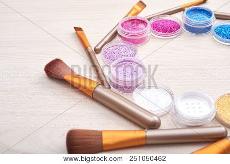 Composition Of Vivid Cans With Shiny Glitters And Makeup Brushes On Wooden Table In Bright Light