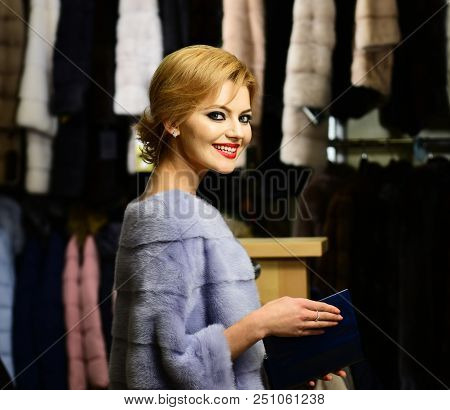Woman With Blond Hair Buys Furry Coat. Girl With Happy Face Wears Furry Coat On Clothes Rack Backgro