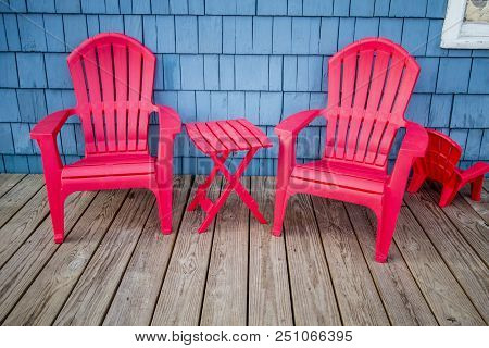 Adirondack Tables And Chairs. Colorful Adirondack Chairs On A Wooden  Outdoor Deck.