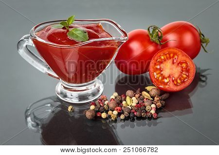 Glass Sauce-boat. Gravy Boat. Tomato Sauce On A Black Background