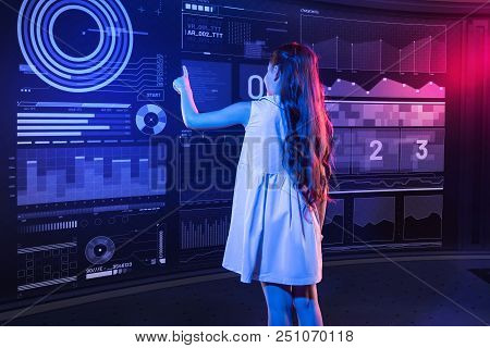 One Touch. Clever Progressive Girl Standing In Front Of A Transparent Device And Touching The Icon O
