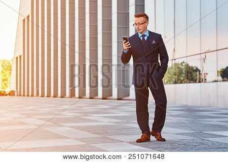 Full Body Portrait Of A Confident Businessman Dressed In An Elegant Suit Using A Phone While Standin