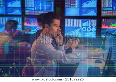 Double exposure of charts with stock exchange broker working in office